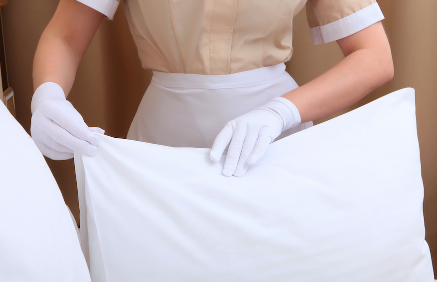 Hotel maid is making the bed wearing gloves post Covid-19