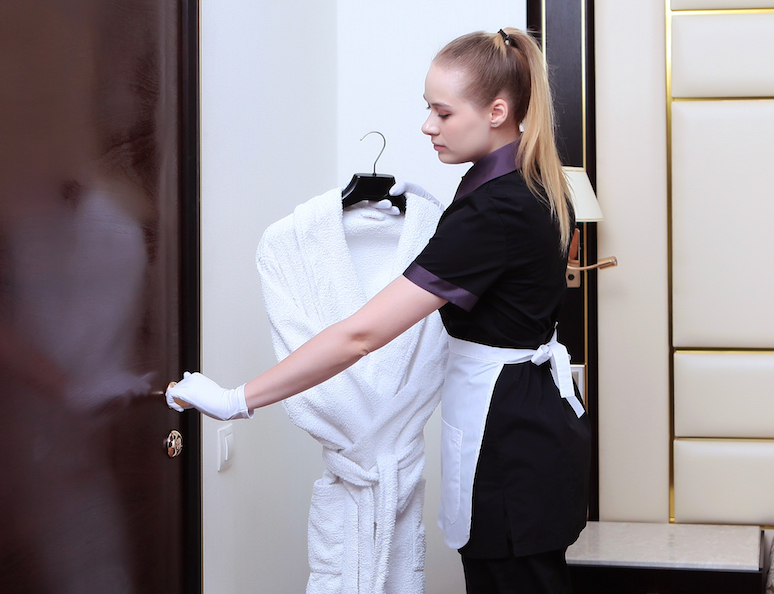 Hotel maid it putting a luxury robe into the closet post Covid-19